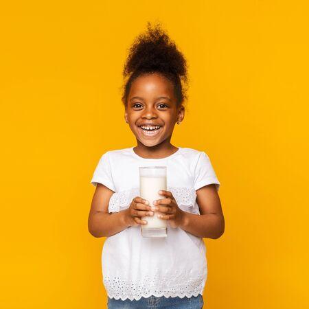 Benefits of dairy products drinking. Cute afro girl enjoying glass of milk, orange studio background