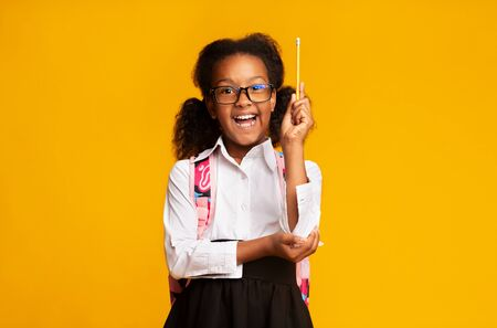Happy Afro Primary School Girl Raising Hand Holding Pencil Knowing Answer On Yellow Background. Studio Shot, Empty Space