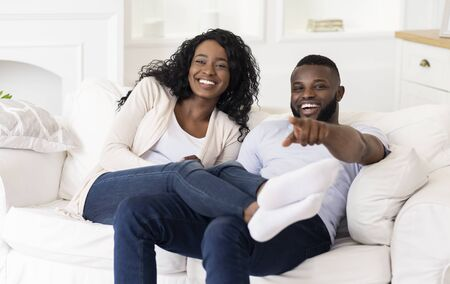 Look at him. Joyful black couple emotionally watching comedy movie on tv, enjoying weekend at home.