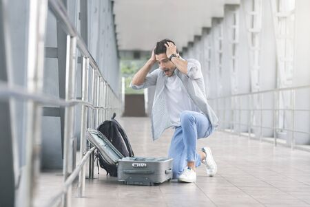 Oh no! Desperate and shocked passenger checking his luggage, looking into empty suitcase at airport, free space 版權商用圖片