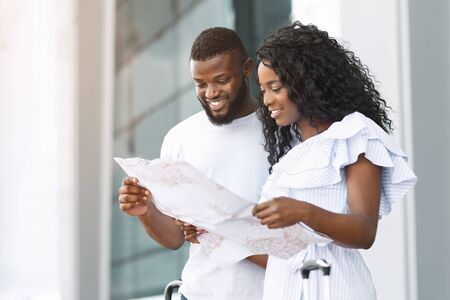 Planning vacation. Cheerful black couple reading map at airport building, free space