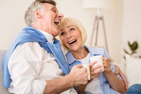 Felice coppia senior che si gode il tè e ride, conversando sul divano di casa