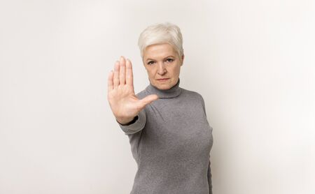 No means no. Portrait of serious elderly woman showing stop gesture standing with stretched hand, light studio background with copy space