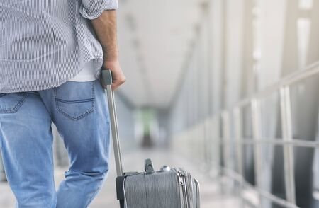 At airport. Man with luggage standing in terminal walkway, preparing for flight, empty space