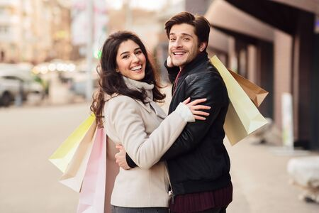 Loving couple with shopping bags embracing outdoors the city center and smiling to camera