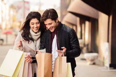 Excited couple looking into shopping bags, enjoying time together after shopping Фото со стока - 129939179