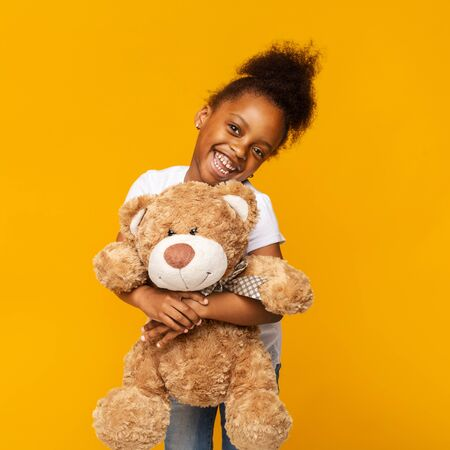 Shy african american little girl embracing her teddy bear and smiling, orange studio background 写真素材