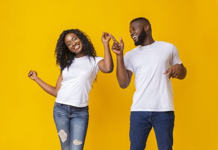 Young black couple dancing together over yellow studio background