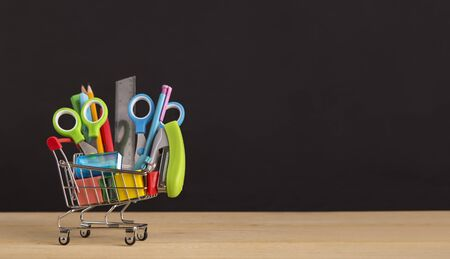 Shopping cart with school supplies over chalkboard background, panorama, copy space 写真素材