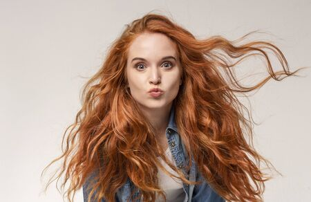 Redhead Girl Sending Air Kiss to Camera, Pouting Lips Over Light Studio Background