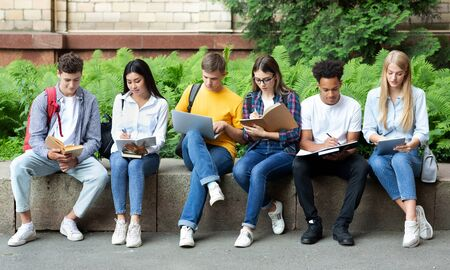 College classmates preparing for lecture, sitting in university campus with books and devices