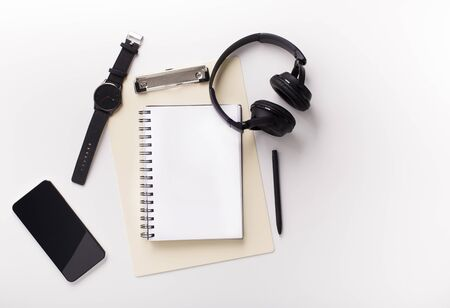 Must have for creation. Cellphone, notebook and headphones on white background