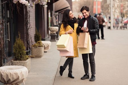 Consumerism concept. Young couple using smartphone outdoors, walking with paper bags