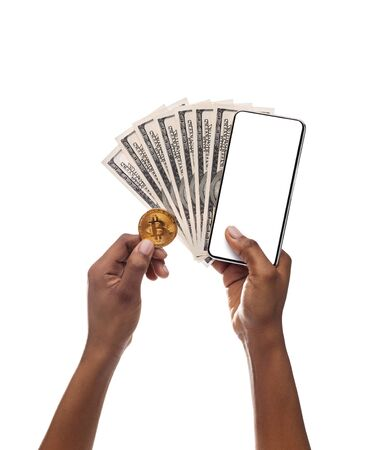 Value of Bitcoin. Black businesswoman holding golden BTC coin, smartphone with blank screen and cash, isolated on white background