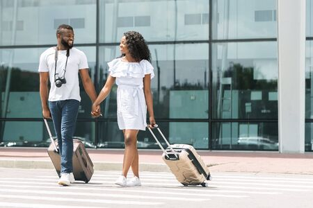 Happy black millennials going out of airport with luggage, free space