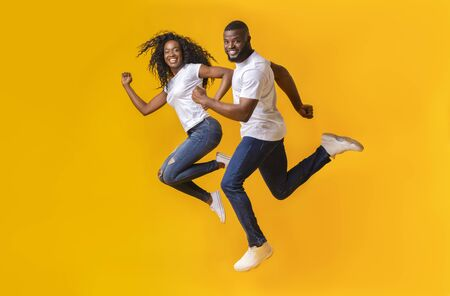 Joyful African American Man And Woman Are Running In The Air, yellow studio background Фото со стока