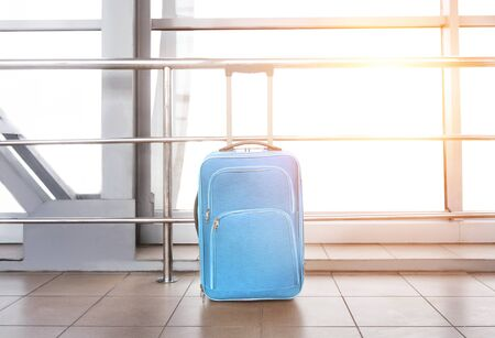 Travel concept. Blue suitcase at airport building, against window with sun flare, free space Stock Photo