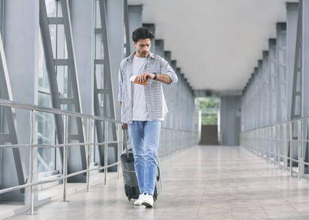 Quizás después. Turista preocupado comprobando el tiempo de servicio, yendo en la pasarela del aeropuerto, espacio vacío