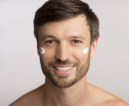 Male Skincare. Unshaven Man Applying Anti-Aging Cream On Face Skin Over White Studio Background. Isolated