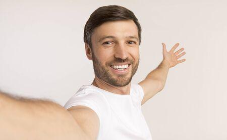 Kijk hiernaar. Glimlachende Man Nemen Selfie Gebaren Met Handen Iets Achter Hem Op Witte Studio Achtergrond Tonen. Geïsoleerd