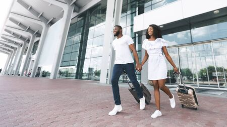 Lets go to trip! Happy african american couple running with luggage at airport exterior, panorama, empty space
