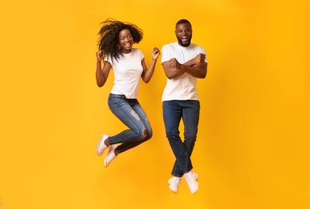 Funny black couple jumping in the air over yellow studio background, posing at camera, copy space