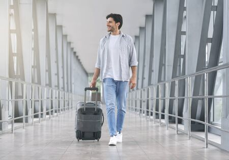 Young man walking in airport walkway with luggage, free space