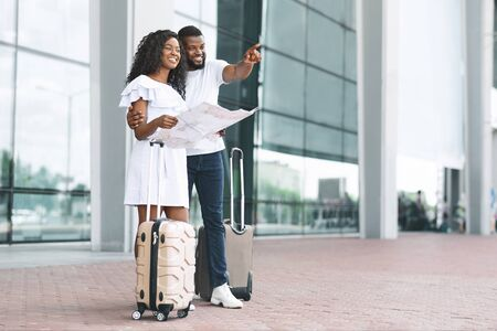 Lets go there. Young black couple planning vacation route, standing with map at airport exterior, guy point aside, empty space