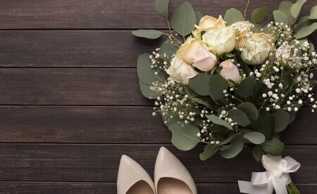 Wedding bouquet and high heel shoes for bride on wooden background, copy space