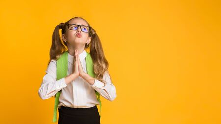Cute Elementary Student Girl Asking For Something Praying With Clasped Hands Over Yellow Background In Studio. Panorama, Free Space