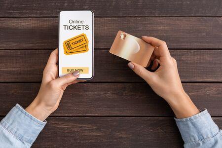 Donna che acquista biglietti per eventi tramite app su smartphone e carta di credito, sfondo in legno scuro Archivio Fotografico
