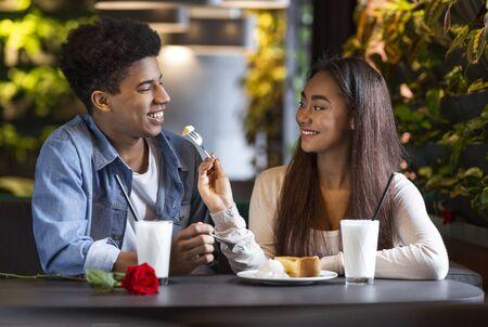 Ugryź. Ładna nastolatka karmi swojego afrykańskiego chłopaka sernikiem w kawiarni Zdjęcie Seryjne