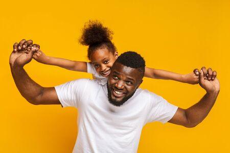 Gelukkig familiespel. Vrolijk klein Afrikaans Amerikaans meisje dat op papa's rug rijdt, oranje achtergrond