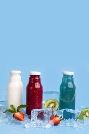 Healthy detox drinks of fresh ingredients on blue background with copy space and ice cubes, vertical panorama