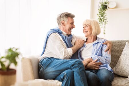 Senior affectionate couple relaxing and looking at each other on sofa at home Archivio Fotografico - 129939453