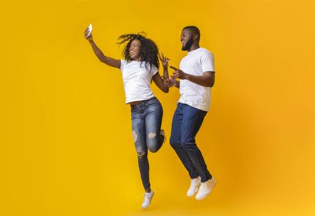 Smiling African Couple Is Taking Selfie While Jumping, pointing at camera, showing victory sign, yellow studio background