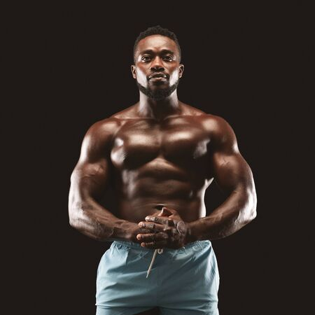 Portrait of muscular african sportsman demonstrating his body over black background, clenching hands together