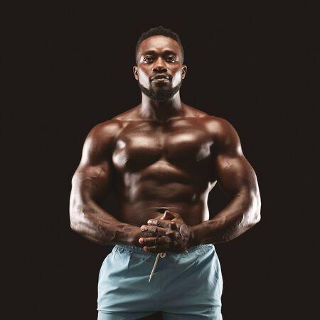 Retrato de deportista africano musculoso mostrando su cuerpo sobre fondo negro, apretando las manos juntas