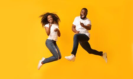 Carefree Black Millennial Couple Jumping In The Air, girl pointing at camera, guy showing thumbs up, yelllow background, panorama Фото со стока
