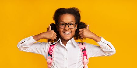Like. Smiling African American School Girl Gesturing Thumbs-Up With Both Hands On Yellow Background In Studio. Panorama