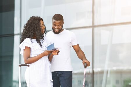 African millennial couple enjoying future adventure, standing with passports near airport building, free space