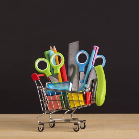 Close up of shopping cart with school stationery for sale over chalkboard background