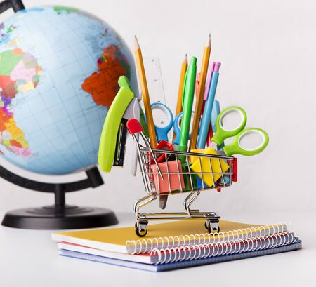 Sale of supplies. Shopping cart with school stationery with world globe on white background