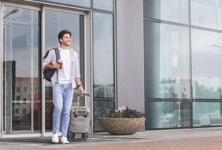 Enjoying long-awaited rest. Happy guy going out of airport building with luggage, copy space