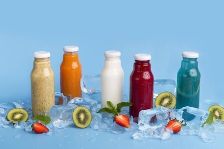 Diet and detox concept. Different types and flavors summer tasty cocktails in glass bottles on blue background