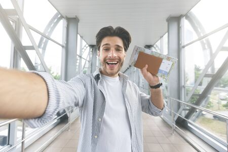 Im going to trip! Excited guy taking selfie with passport and tickets at airport