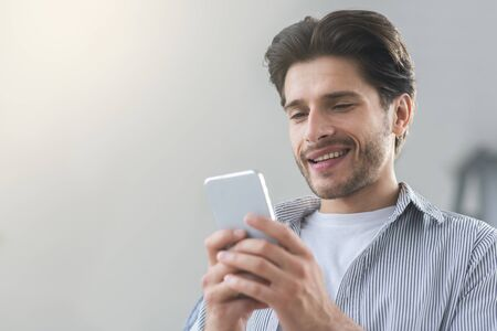 Cheerful millennial man texting with friend on cellphone, empty space