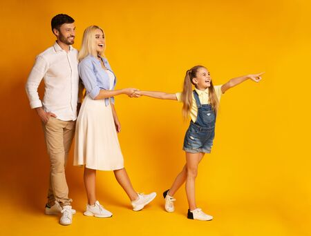 Entretenimiento familiar. Hija emocionada que señala el dedo mostrando algo a los padres caminando juntos. Fondo amarillo, tiro del estudio Foto de archivo