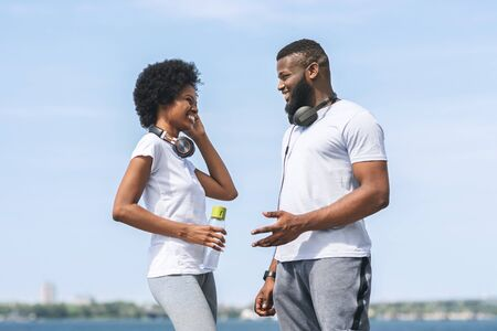 Afro Man And Woman Talking After Morning Jog Near River In City. Coaching And Running Concept.