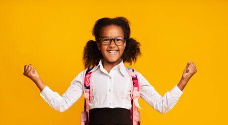 Excited African American Schoolgirl Gesturing Yes Rejoicing Success On Yellow Background In Studio. School Winner Imagens